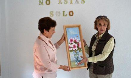 La pintora Puerto Encinas entrega a AOEX Plasencia un cuadro para el próximo mercadillo benéfico