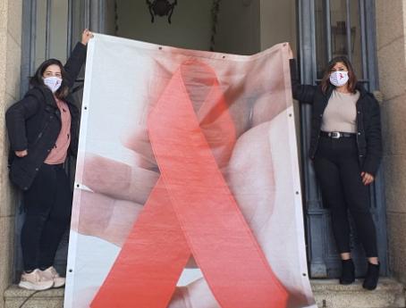 Cáceres lucha contra el Sida con un lazo rojo en la fachada del ayuntamiento